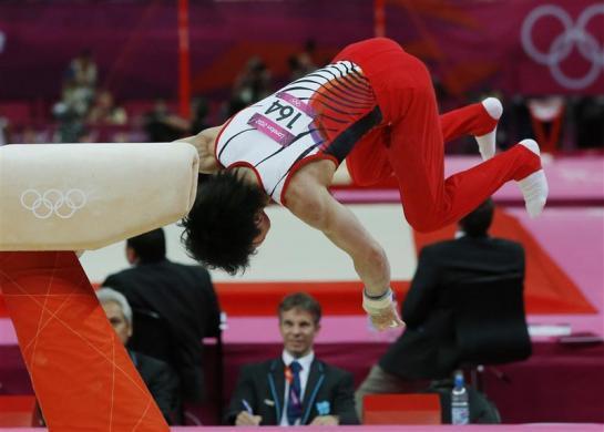 A judge watches as Kohei Uchimura of Japan falls off the pommel horse during the men's gymnastics team final in the North Greenwich Arena during the London 2012 Olympic Games July 30, 2012.