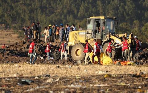 Members of the search and rescue mission carry dead bodies at the scene of the Ethiopian Airlines Flight ET 302 plane crash, near the town of Bishoftu - Credit: Reuters