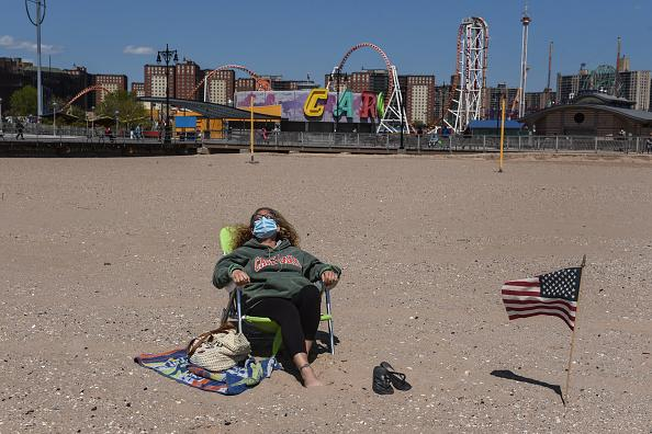 A person sunbathes while wearing a protective mask in the Coney Island neighbourhood in the Brooklyn borough in New York City.