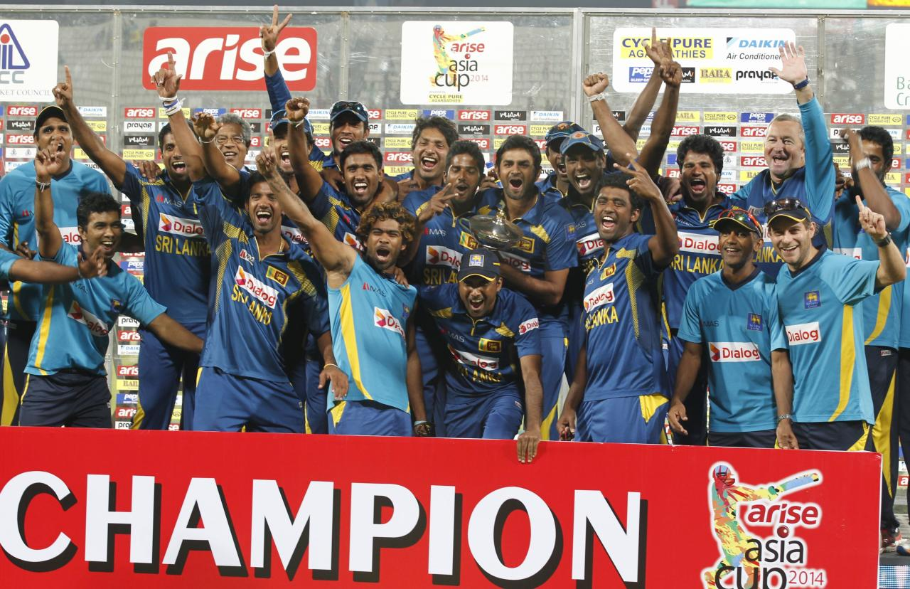 Sri Lanka's fielders pose with the winning trophy after Sri Lanka won the 2014 Asia Cup final against Pakistan in Dhaka March 8, 2014. REUTERS/Andrew Biraj (BANGLADESH - Tags: SPORT CRICKET)