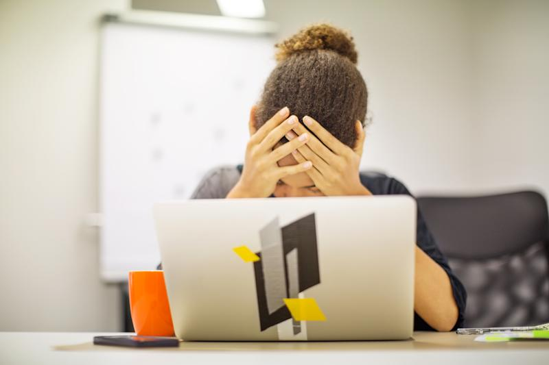 Depressed female professional in panic holding head in hands in front of laptop. Businesswoman frustrated by bad new at office desk.