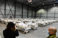 A journalist takes a picture of beds prepared in a field hospital, which will function as a backup device for patients with coronavirus, in the Letnany neighbourhood at the Prague outskirts, Czech Republic, Thursday, Oct. 22, 2020. (AP Photo via CTK/Roman Vondrous) SLOVAKIA OUT