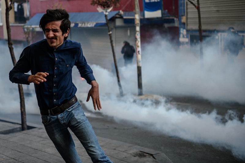 People run away from tear gas the Turkish anti-riot police fired on March 11, 2016 in Istanbul as people gathered to mark the second anniversary of the death of the youngest victim of the Gezi Park protests