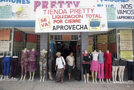 """Women leave a clothing store with a big sign reading """"Store Pretty, total closing down sale, take advantage"""" in Arecibo, Puerto Rico, June 29, 2015. REUTERS/Alvin Baez-Hernandez"""
