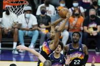 Phoenix Suns forward Mikal Bridges, top left, grabs a rebound against the Los Angeles Clippers as Suns forward Cameron Johnson, center, and center Deandre Ayton, right, look on during the second half of Game 1 of the NBA basketball Western Conference finals Sunday, June 20, 2021, in Phoenix. (AP Photo/Ross D. Franklin)
