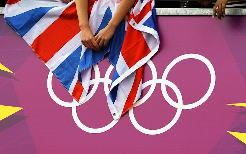 A cycling fan holds a British flag over the Olympic Rings logo during the men's Road Cycling Race at the London 2012 Olympic Games - Shutterstock