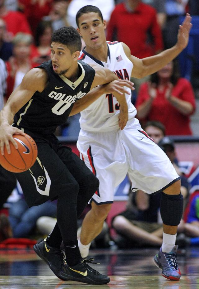 Colorado's Askia Booker (0) barely gets away from the pressing defense of Arizona's Nick Johnson (13) in the first half of an NCAA college basketball game, Thursday, Jan. 23, 2014 in Tucson, Ariz. (AP Photo/John Miller)