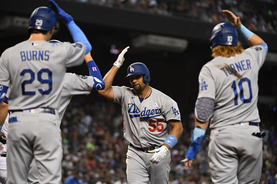 Albert Pujols of the Los Angeles Dodgers celebrates with Justin Turner and Andy Burns after hitting a three-run home run. (Photo by Norm Hall/Getty Images)