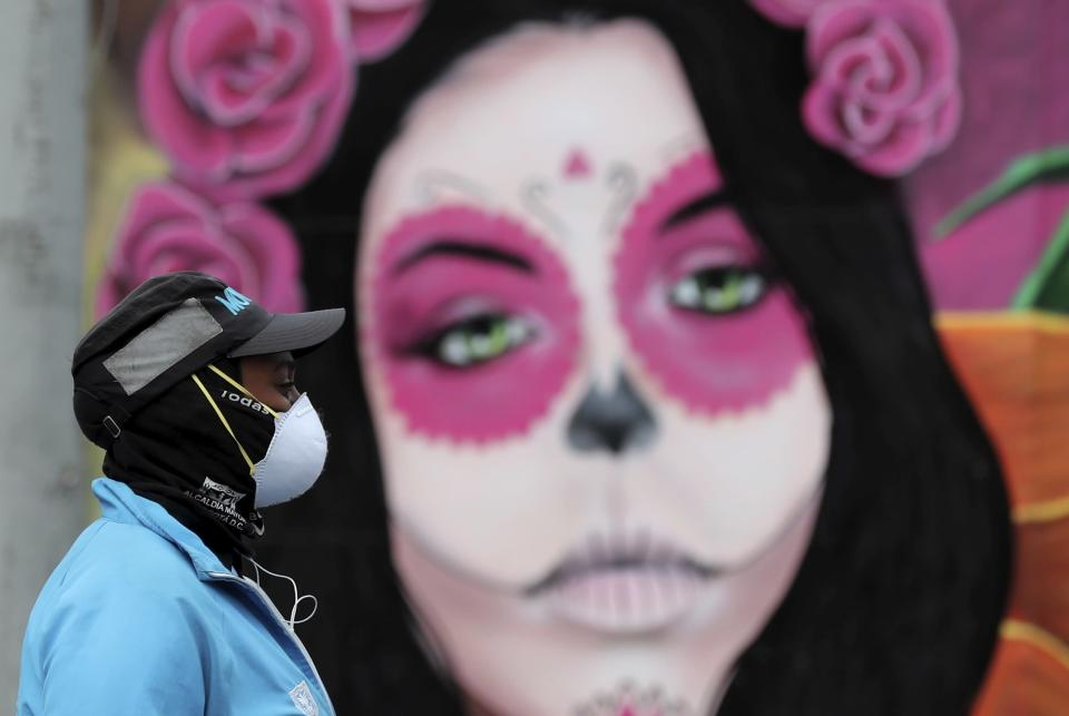 A woman wearing a face mask amid the spread of the new coronavirus walks past a Catrina mural in Bogota, Colombia, Thursday, May 21, 2020. (AP Photo/Fernando Vergara)