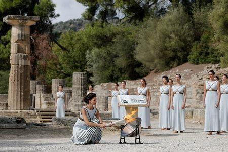 Olympics - Dress Rehearsal - Lighting Ceremony of the Olympic Flame Pyeongchang 2018 - Ancient Olympia, Olympia, Greece - October 23, 2017 Greek actress Katerina Lehou, playing the role of High Priestess, lights a torch from the sun's rays reflected in a parabolic mirror during the dress rehearsal for the Olympic flame lighting ceremony for the Pyeongchang 2018 Winter Olympic Games at the site of ancient Olympia in Greece REUTERS/Alkis Konstantinidis