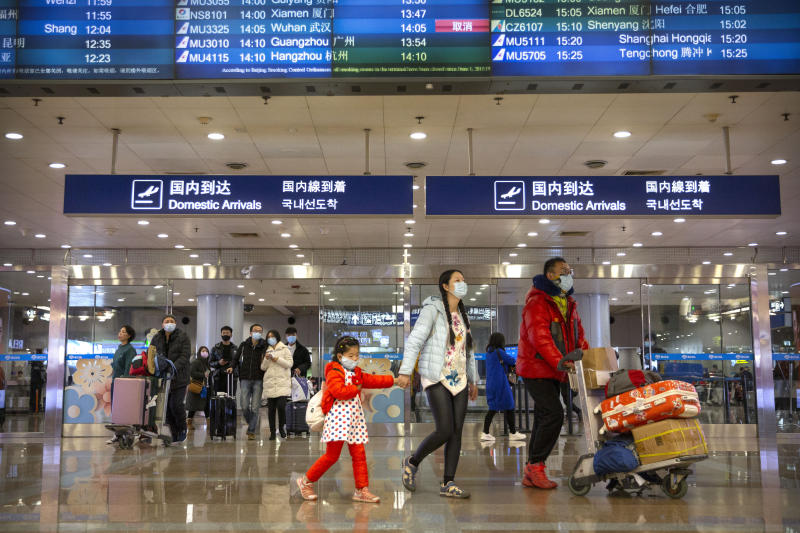 Travelers in face masks walk past a display board showing a canceled flight from Wuhan at Beijing Capital International Airport in Beijing, Thursday, Jan. 23, 2020. China closed off a city of more than 11 million people Thursday, halting transportation and warning against public gatherings, to try to stop the spread of a deadly new virus that has sickened hundreds and spread to other cities and countries in the Lunar New Year travel rush. (AP Photo/Mark Schiefelbein)