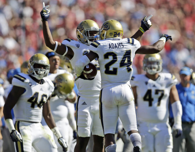 UCLA cornerback Ishmael Adams (24) celebrates with teammate Jayon Brown after intercepting a pass against Stanford during the first half of an NCAA college football game on Saturday, Oct. 19, 2013, in Stanford, Calif. (AP Photo/Marcio Jose Sanchez)
