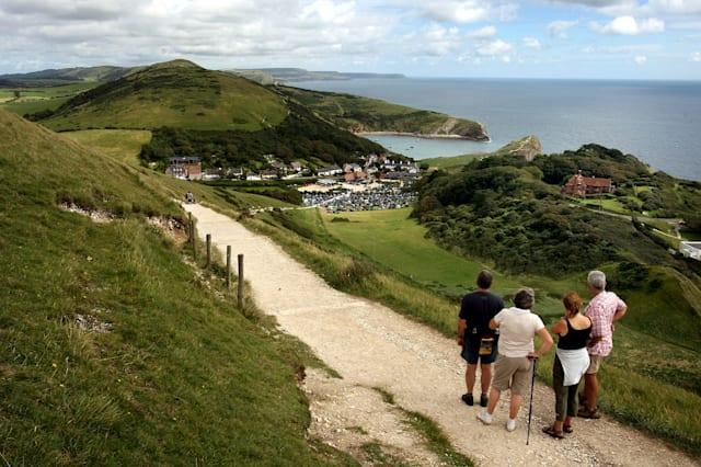 """File photo dated 13/08/07 of walkers on the coastal path leading from Lulworth Cove to Durdle Door in West Lulworth, Dorset as trading just two minutes of sitting for walking can help you live longer, scientists claim. PRESS ASSOCIATION Photo. Issue date: Friday May 1, 2015. Getting motivated for that much time of every hour otherwise spent languishing on a sofa or remaining stuck behind a desk reduced the risk of dying by a third, a study found. For people with chronic kidney disease, the swap was even more effective, lowering mortality by 41%. Scientists used statistical techniques to examine the effect of """"trading off"""" sedentary behaviour for different levels of activity. Standing instead of sitting for two minutes every hour produced no benefit. But trading sitting time for """"light activity"""", such as casual walking or housework, had a significant impact. See PA story HEALTH Walking. Photo credit should read: Anthony Devlin/PA Wire"""