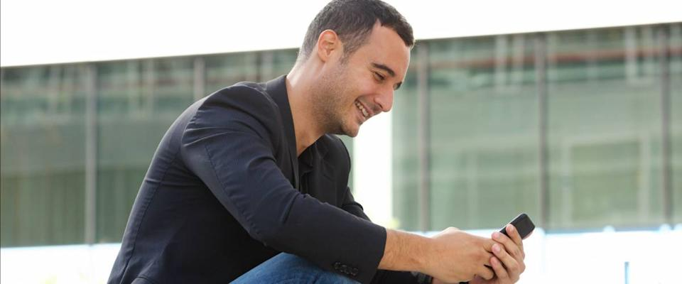 Portrait of smiling man sitting outside and looking at mobile phone