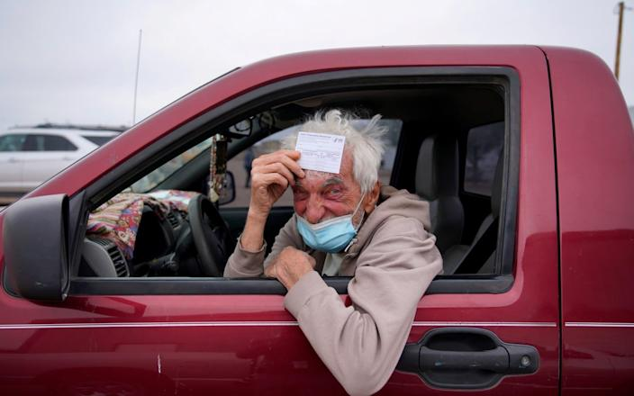 Taras Mychalewych, 75, poses for a portrait with his vaccination card after receiving his Covid-19 vaccine at a rural vaccination site in Columbus, New Mexico - PAUL RATJE/REUTERS