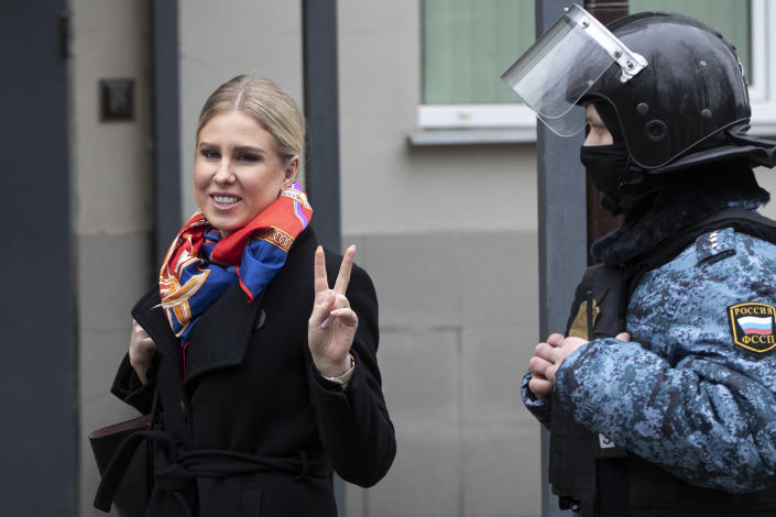 Russian opposition activist Lyubov Sobol gestures as she walks to the court escorted by a Russian Federal Bailiffs service officer in Moscow, Russia, Monday April 5, 2021. A Moscow court will start considering the case against Navalny ally Lyubov Sobol, who is charged with unlawful entry into a dwelling. In December Sobol rang the doorbell of a flat of a relative of an alleged FSB agent Konstantin Kudryavtsev, whom Navalny accused of his poisoning. (AP Photo/Pavel Golovkin)
