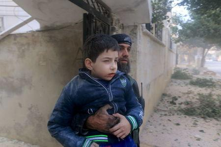A rescue worker holds an injured boy after what activists said were airstrikes carried out by the Russian air force in Idlib city