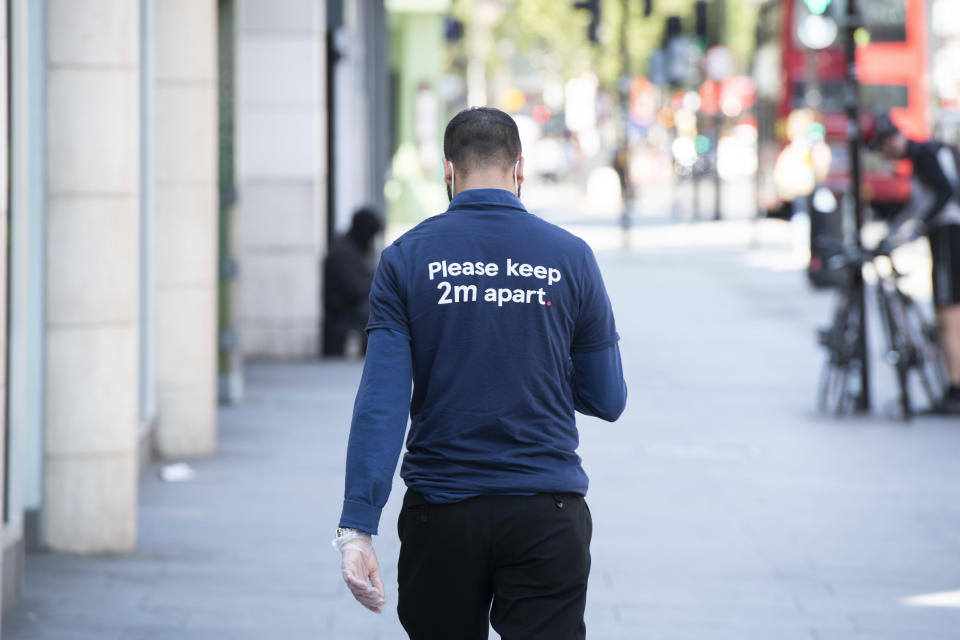 A shop worker wears a t shirt saying 'Please keep 2m apart' to respect social distancing, during the Coronavirus outbreak, Tottenham Court Road, London.  Picture date: Tuesday 21st April 2020.  Photo credit should read:  David Jensen/ EMPICS Entertainment