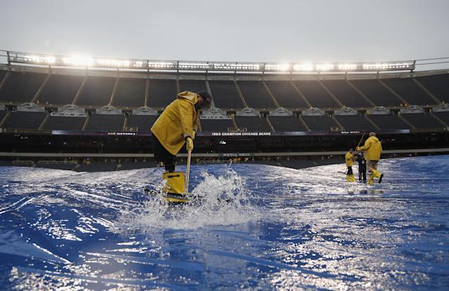 Stadium employees push rain water off the tarp at Soldier Field before an NFL football game between the Chicago Bears and Minnesota Vikings, Sunday, Sept. 15, 2013, in Chicago. (AP Photo/Charles Rex Arbogast)