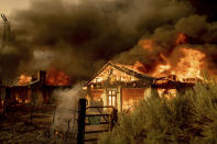 Fire consumes homes as the Sugar Fire, part of the Beckwourth Complex Fire, tears through Doyle, Calif., on Saturday, July 10, 2021. Pushed by heavy winds, the fire came out of the hills and destroyed multiple residences in central Doyle. (AP Photo/Noah Berger)