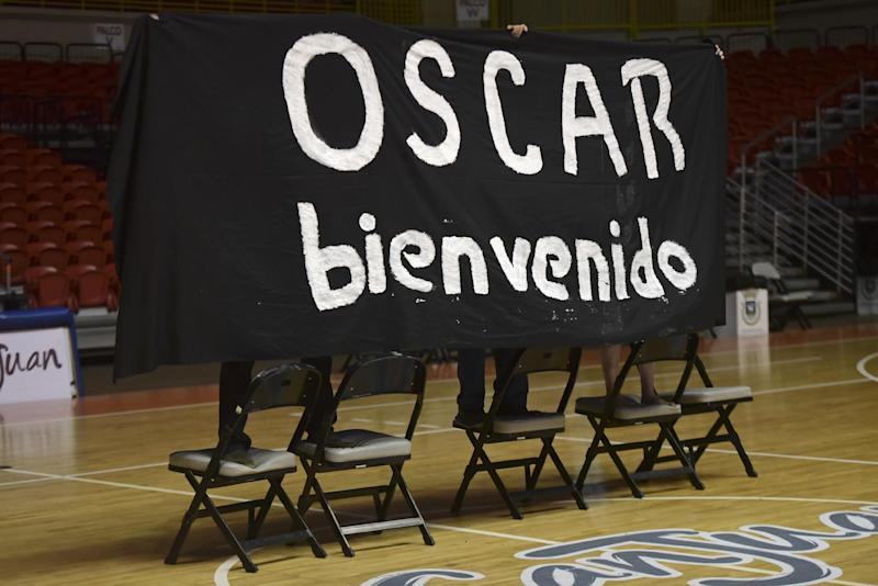 Supporters hold up a sign during a press conference to welcome home Puerto Rican nationalist Oscar Lopez Rivera on the day he returned to San Juan, Puerto Rico, Thursday, Feb. 9, 2017. Rivera unexpectedly returned to the island on Thursday to serve the remainder of a sentence commuted by outgoing U.S. President Barack Obama, according to the San Juan mayor's office. (AP Photo/Carlos Giusti)