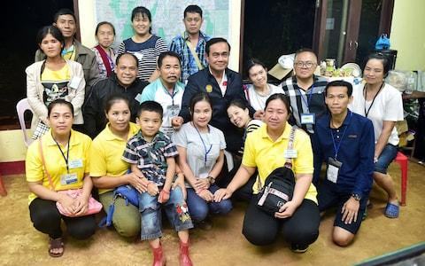 <span>Thailand's prime minister Prayuth Chan-ocha poses with relatives of boys who have been trapped in the flooded cave</span> <span>Credit: REUTERS </span>
