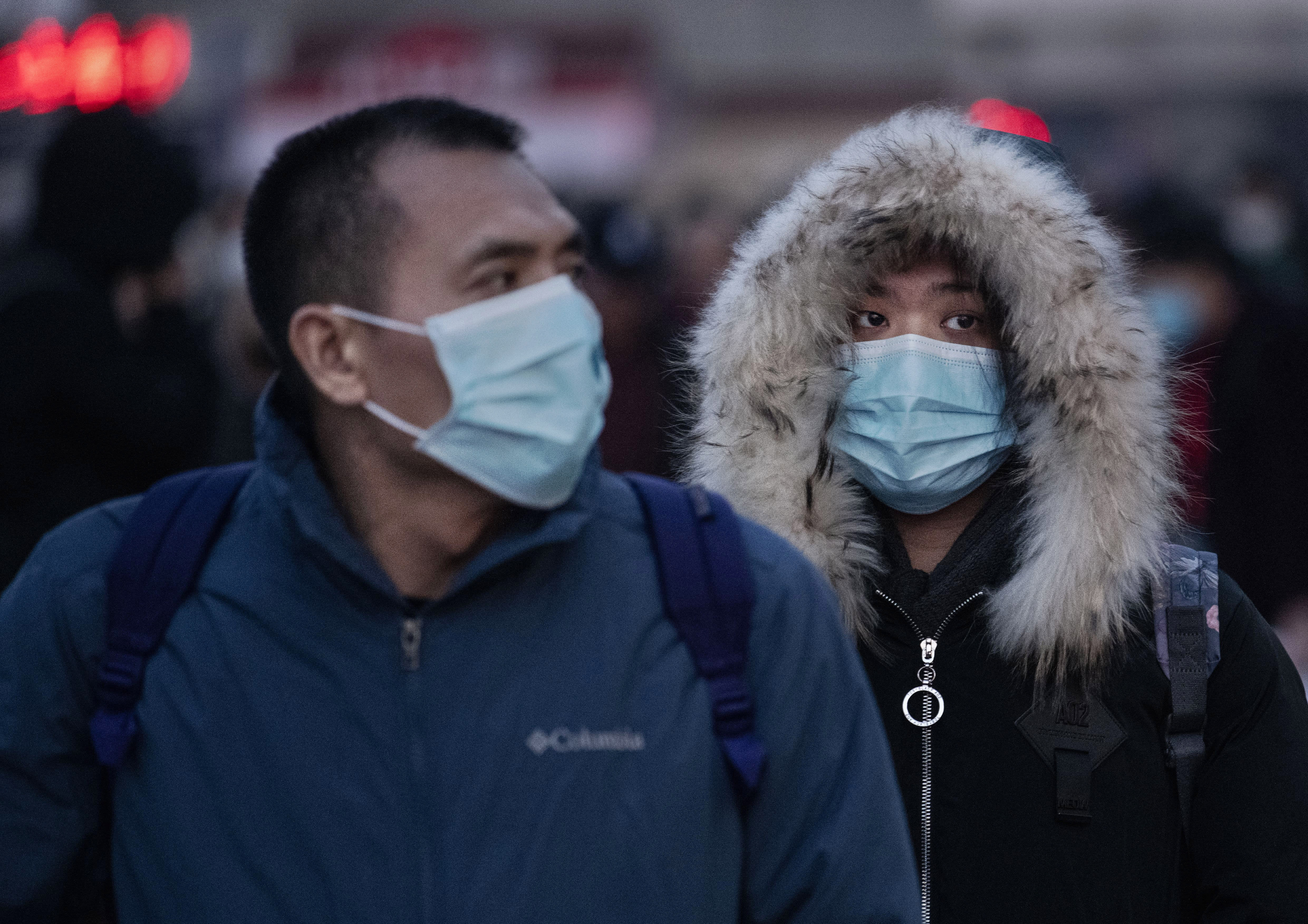 BEIJING, CHINA - JANUARY 21: Chinese travellers wear protective masks as they arrive to board trains at Beijing Railway station before the annual Spring Festival on January 21, 2020 in Beijing, China. The number of cases of a deadly new coronavirus rose to nearly 300 in mainland China Tuesday as health officials stepped up efforts to contain the spread of the pneumonia-like disease which medicals experts confirmed can be passed from human to human. The number of those who have died from the virus in China climbed to six on Tuesday and cases have been reported in other parts of Asia including in Thailand, Japan, Taiwan and South Korea. (Photo by Kevin Frayer/Getty Images)