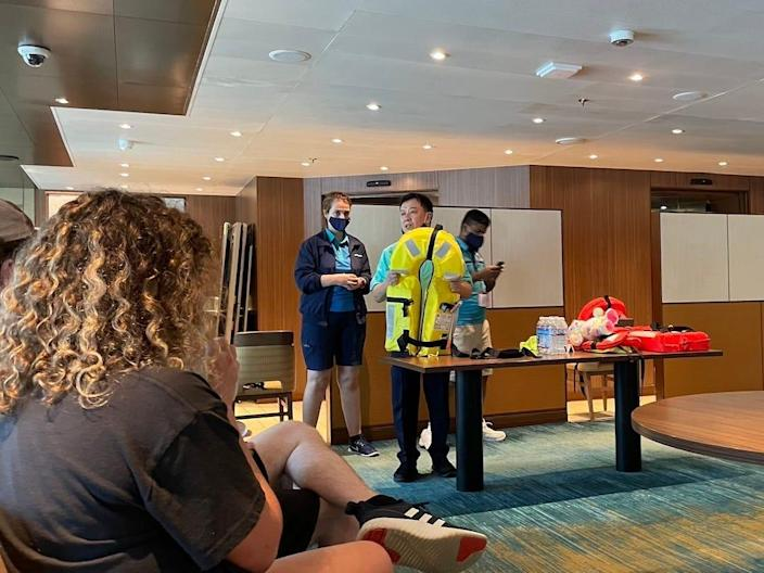 Cruise ship crew members show passengers how to properly put on a life vest during the muster drill.