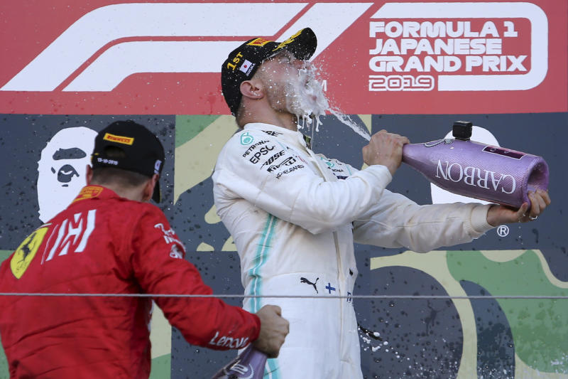 In this Sunday, Oct. 13, 2019, file photo, Mercedes driver Valtteri Bottas of Finland pours champagne to himself next to second placed Ferrari driver Sebastian Vettel, left, of Germany on the podium after winning the Japanese Formula One Grand Prix at Suzuka Circuit in Suzuka, central Japan. (AP Photo/Toru Takahashi, File)