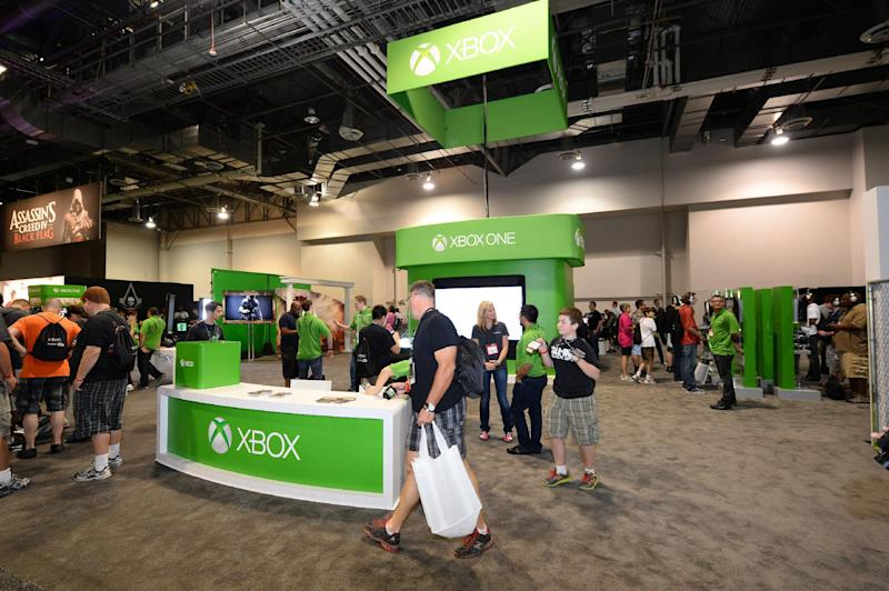FILE - In this Aug. 28, 2013 file photo, attendees stop by the Microsoft Xbox booth at the GameStop Expo in Las Vegas. When it comes to hyping next-generation hardware, the video game industry doesn't typically opt for simplicity. However, during a presentation at the GameStop Expo to promote the upcoming Xbox One console last week, a no-frills approach is exactly what Microsoft employed when confronted with a convention room full of passionate gamers. (Photo by Al Powers/Invision/AP, File)