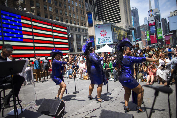 Selena Quinn, from left, LaVon Fisher-Wilson and Traci Coleman perform during a free outdoor event organized by The Broadway League as Juneteenth's celebrations take place at Times Square Saturday, June 19, 2021, in New York. Parades, picnics and lessons in history marked Juneteenth celebrations in the U.S., a day that marks the arrival of news to enslaved Black people in a Texas town that the Confederacy had surrendered in 1865 and they were free. (AP Photo/Eduardo Munoz Alvarez)
