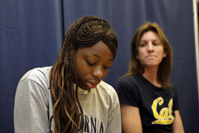 FILE - In this Oct. 9, 2009, file photo, California freshman forward Tierra Rogers, left, is emotional during an NCAA basketball news conference as head coach Joanne Boyle, right, watches her in Berkeley, Calif. Rogers, who never played a single minute because of a rare heart condition that could have killed her, has that diploma in hand at last, four years after a frightening collapse that derailed her college career before it began. The highly touted guard stopped breathing outside the Cal training room in Sept. 2009. (AP Photo/Paul Sakuma, File)