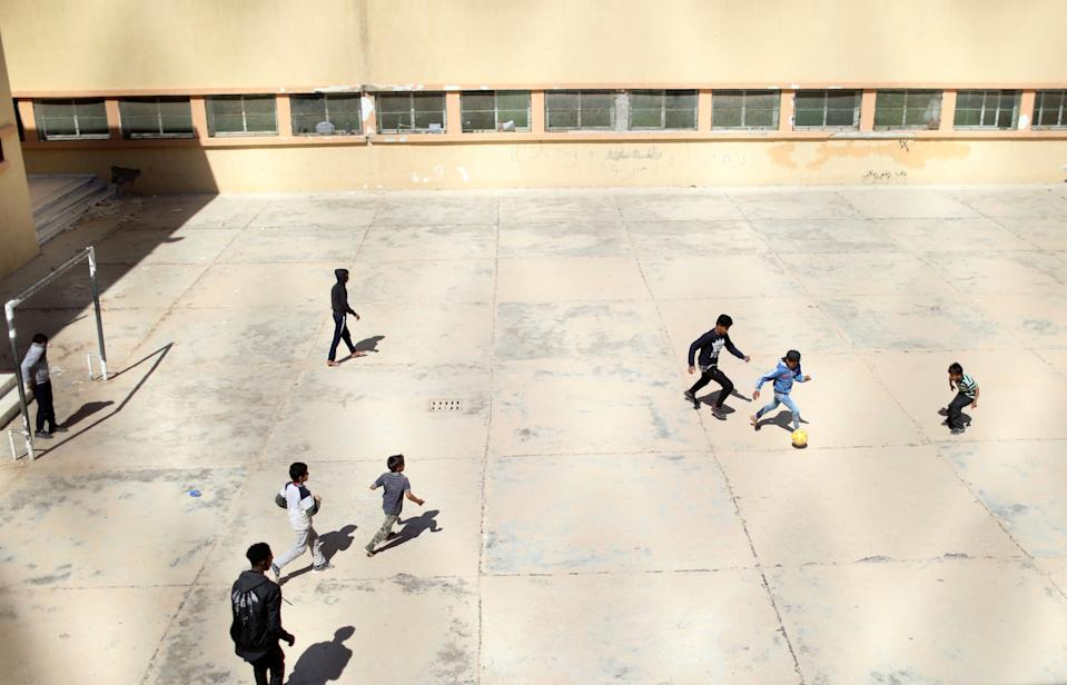 Libyan displaced boys, who fled their house because of the fighting between the Eastern forces commanded by Khalifa Haftar and the internationally recognised government, play soccer at Bader School, which is used as a shelter, in Tripoli, Libya April 14, 2019. REUTERS/Ahmed Jadallah