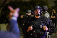 A protestor reacts towards a Portland police officer during protests, Saturday, Sept. 26, 2020, in Portland. The protests which began since the police killing of George Floyd in late May often result frequent clashes between protesters and law enforcement. (AP Photo/John Locher)