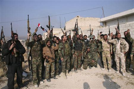 Forces loyal to Syria's President Bashar al-Assad hold up their weapons as they cheer in the town of Safira