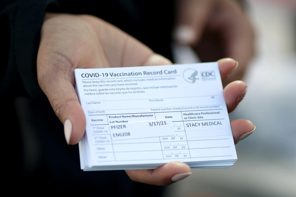 A medical worker holds Pfizer coronavirus disease (COVID-19) vaccination cards at a mobile vaccination drive for essential food processing workers at Rose & Shore, Inc., in Vernon, Los Angeles, California, U.S., March 17, 2021. REUTERS/Lucy Nicholson
