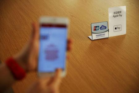 FILE PHOTO: An employee uses the Apple iPhone to demonstrate to reporters how to pay using the Apple Pay service in Beijing