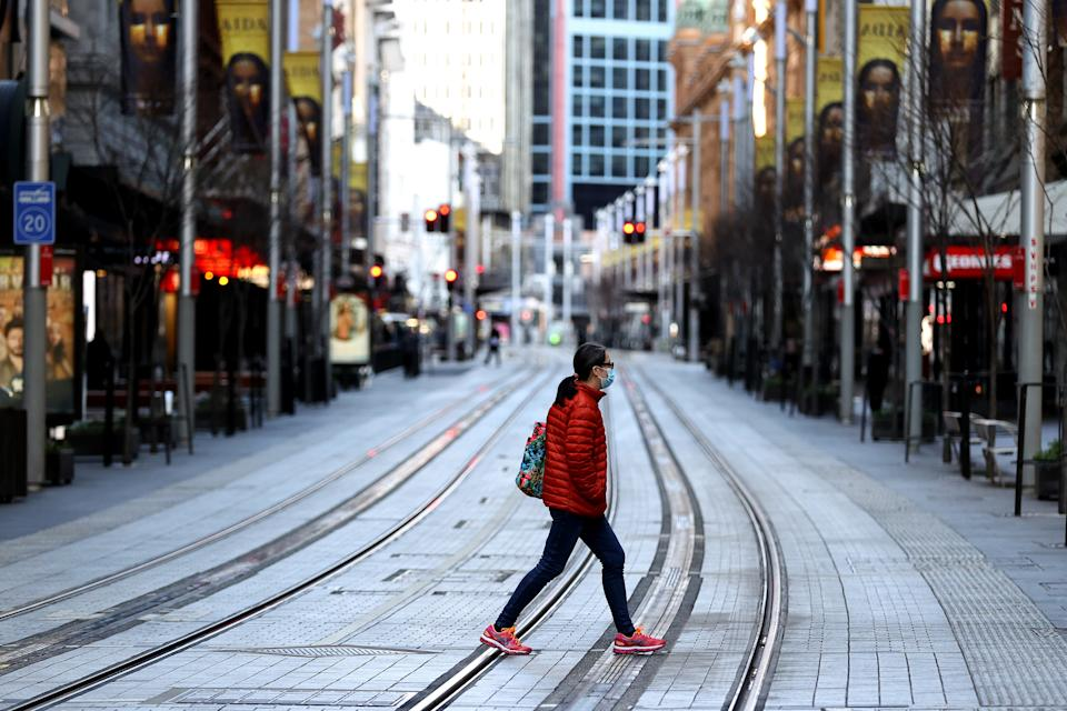 A woman in a red coat crosses George Street in Sydney's CBD.