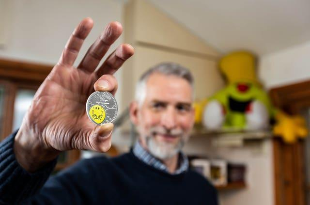 Adam Hargreaves holds a Mr Happy coin