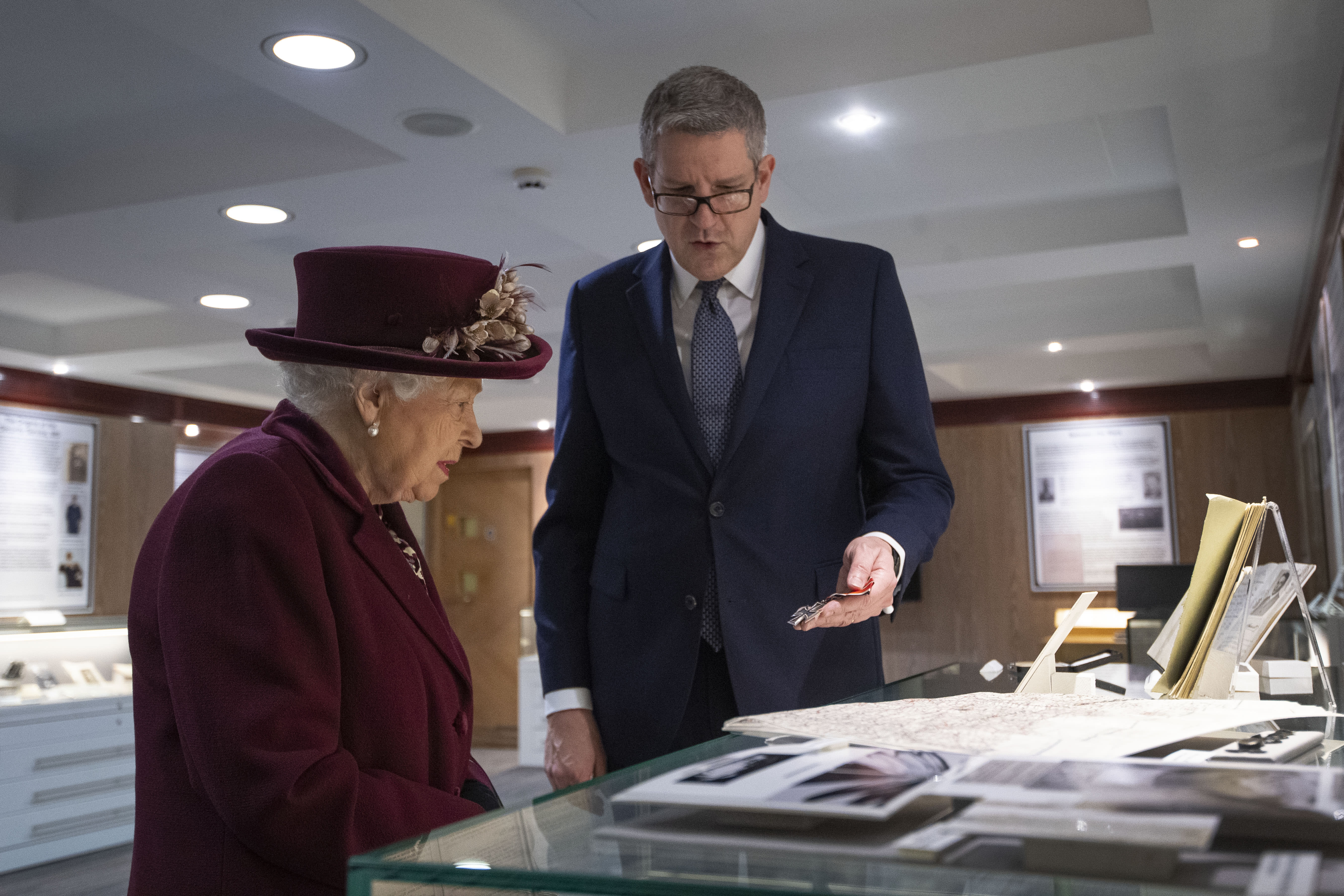 Queen Elizabeth II looks at artifacts relating to MI5 D-Day operations with Director General Andrew Parker during a visit to the headquarters of MI5 at Thames House in London.