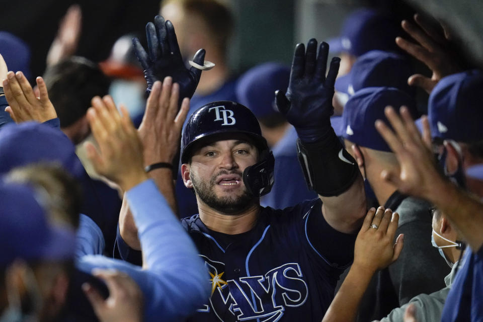 Tampa Bay Rays' Mike Zunino is greeted in the dugout after hitting a two-run home run off Baltimore Orioles relief pitcher Travis Lakins Sr. during the fifth inning of a baseball game, Tuesday, May 18, 2021, in Baltimore. Rays' Yandy Diaz scored on the home run. (AP Photo/Julio Cortez)