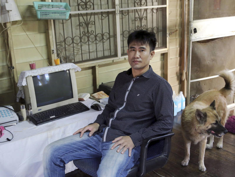 "In this photo taken Sept. 10, 2013, Thanawat Martnok poses for photographer with his dog at his house in Bangkok, Thailand. After having quarreled with his younger brother Yuthapoom Martnok, Thanawat told police that Yuthapoom had defamed King Bhumibol, an accusation that should be punished up to 15 years behind bars. Yuthapoom was indicted on charges of ""lese majeste"" - insulting the royal family. Denied bail on national security grounds, he has been jailed for a year in a Bangkok prison where he is anxiously awaiting the court's verdict Friday, Sept. 13, 2013. (AP Photo/Apichart Weerawong)"