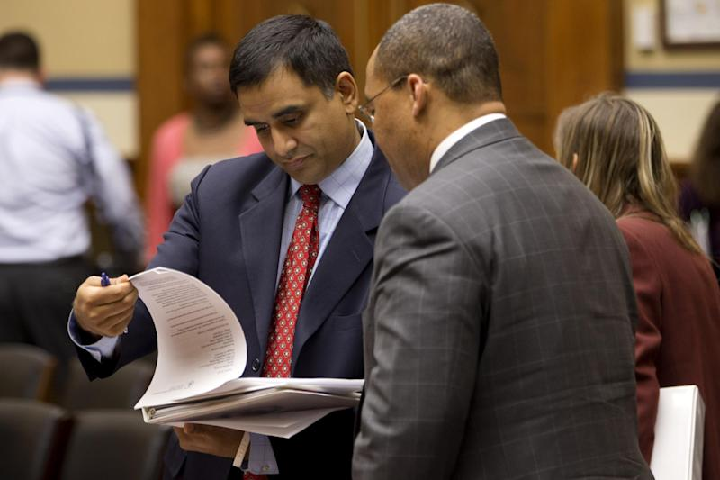 Deputy Commerce Secretary for Resource Management Hari Sastry, left, looks over documents on Capitol Hill in Washington, Tuesday, March 19, 2013, during a break in his testimony in a joint hearing on sequestration held by House Oversight and Government Reform Committee's subcommittee on Economic Growth, Job Creation and Regulatory Affairs, and the subcommittee on Federal Workforce, U.S. Postal Service and the Census.  (AP Photo/Jacquelyn Martin)