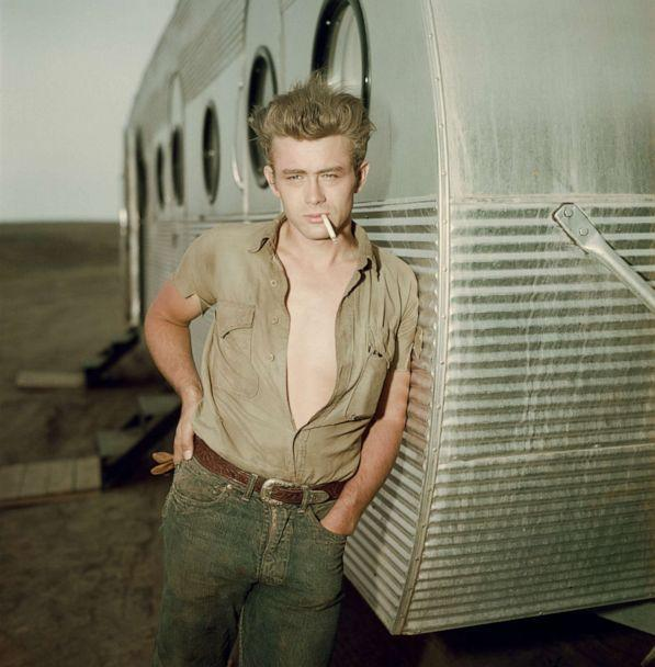 PHOTO: James Dean leans against a dressing room trailer with his shirt open to the waist while smoking a cigarette on the set of director George Stevens's 1956 film, 'Giant.' (Hulton Archive/Getty Images)