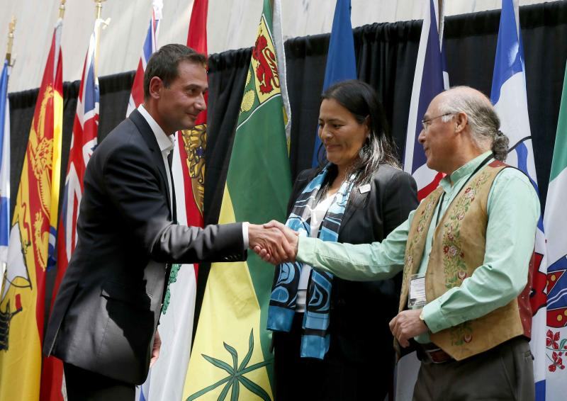 Robert Ghiz shakes hands with Clement Chartier as Michele Audette looks on following a news conference to summarize the meetings of Canada's premiers with National Aboriginal Organization (NAO) leaders in Charlottetown