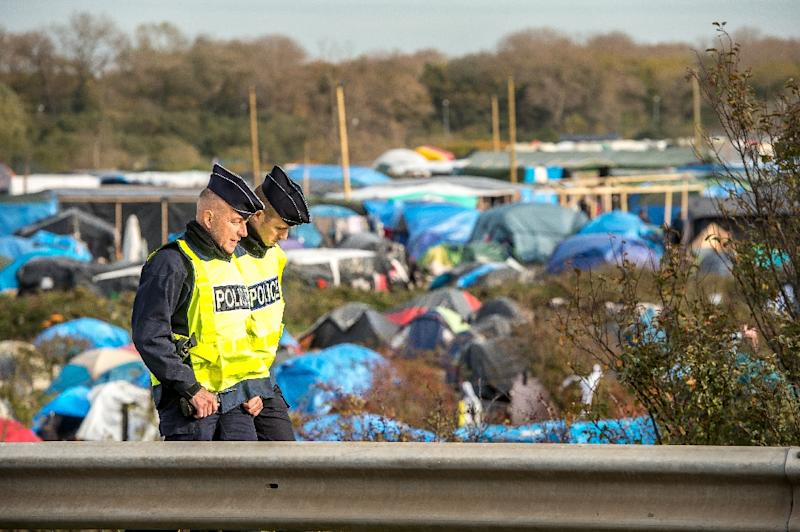 """Policemen patrol on November 5, 2015 in the """"Jungle"""" migrants camp in Calais, northern France"""