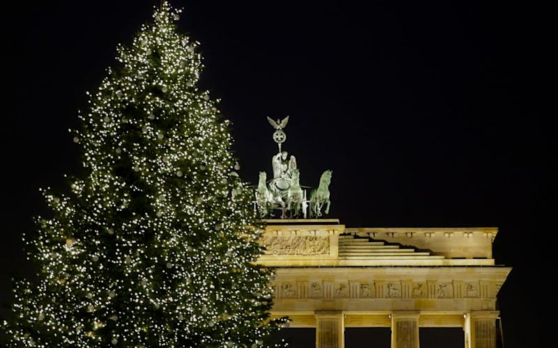 A christmas tree is illuminated in front of Germany's landmark Brandenburg Gate - AP
