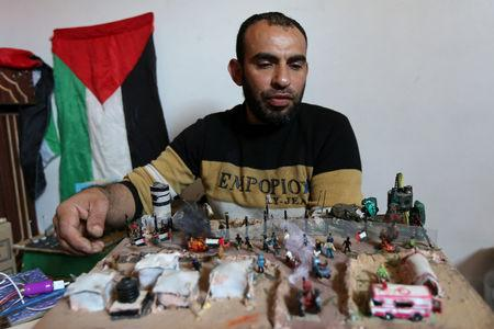 Palestinian diorama artist Majdi Abu Taqeya works on miniature figures he carves from remnants of Israeli ammunition collected from the scenes of border protests along the Israel-Gaza border, in the central Gaza Strip March 11, 2019. Picture taken March 11, 2019. REUTERS/Ibraheem Abu Mustafa