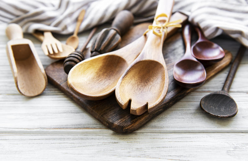 Wooden cutlery kitchen ware on a white wooden background