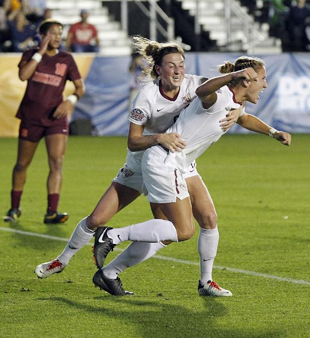 Florida State University's Kristin Grubka, right, and teammate Kassey Kallman celebrate Grubka's first period goal against Virginia Tech in an NCAA college soccer semifinal game at the Women's College Cup soccer tournament in Cary, N.C., Friday, Dec. 6, 2013. (AP Photo/Ellen Ozier)